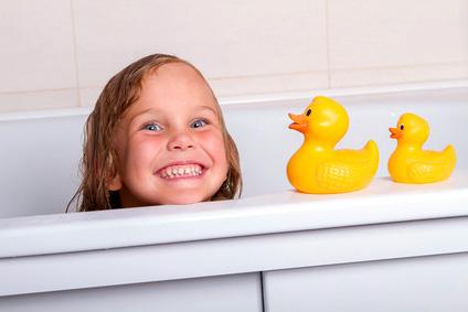 Kleines Mädchen in der Badewanne mit Quietscheenten