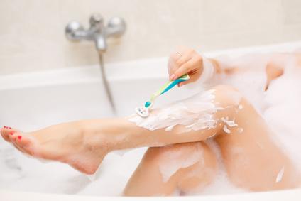 Junge Frau rasiert sich die Beine in der Badewanne