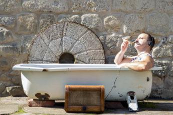 Mann in Badewanne hört Musik