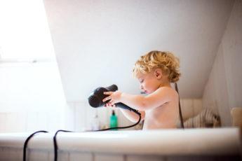 Kleinkind mit Fön an der Badwanne