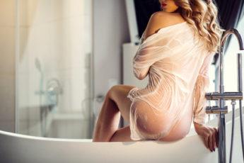 Beautiful sexy lady in elegant white shirt in a bathroom